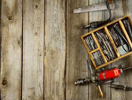 drills: Old working tools. Drills in a box, a drill, a chisel on a wooden background.