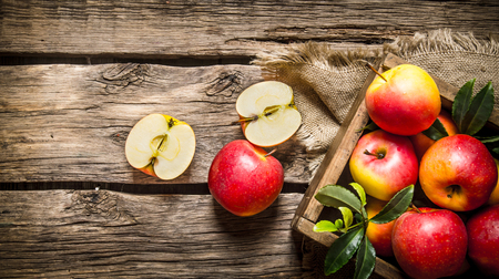 red box: Fresh red apples in wooden box On wooden background. Top view