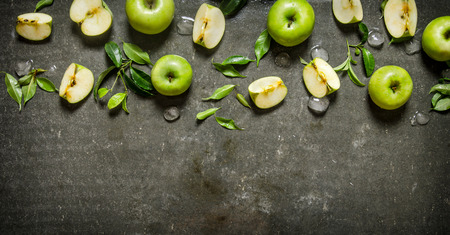 Green apples, whole and sliced with leaves and ice On a rustic stone table.