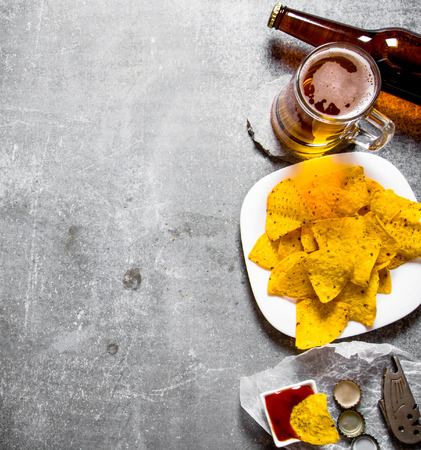 Beer with chips and ketchup On old stone background. Top view