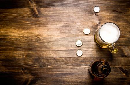 bebidas frias: Botella de cerveza estilo-, cerveza en el vaso y abarca en mesa de madera.