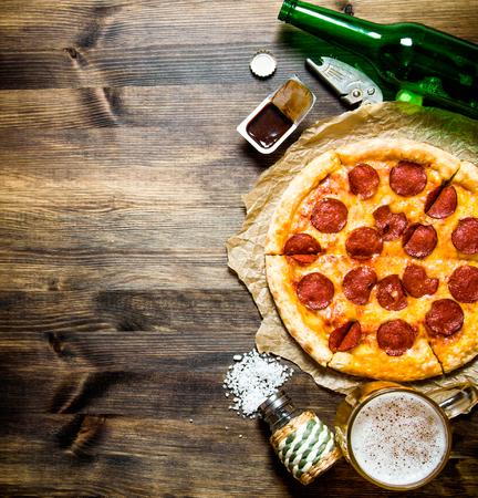 나무 테이블에 맥주와 함께 페퍼로니 피자. 평면도