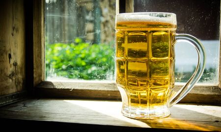 window sill: Glass of fresh beer on an old wooden window sill