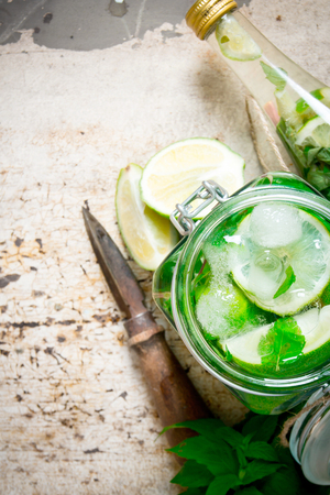 bootle: The cocktail in the jar, the bottle with ice cubes, lime, mint leaves and rum