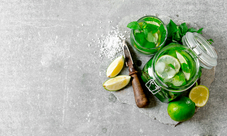lime juice: Cocktail in jar - mint leaves, ice, rum and lime on a stone base with a knife for citrus and sugar