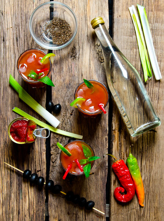 vegetable tin: The cocktail bloody mary. Three cocktail with ingredients - ice, tomatoes, vodka, celery, pepper, olives and mint leaves on a wooden table