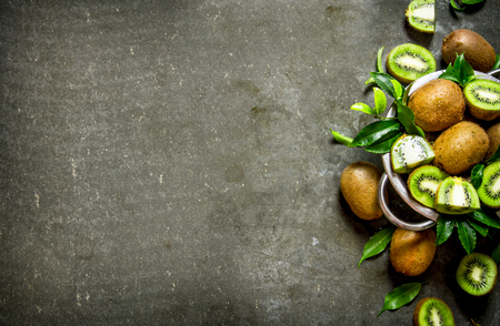 pan tropical: Fresh kiwi fruit in a pan with the leaves On the stone table. Stock Photo