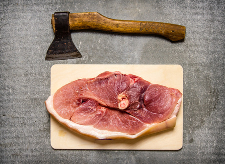 stone cutter: A piece of raw pork with a hatchet for meat cutting On the stone table. Top view