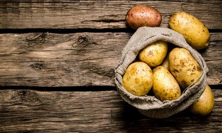papas: patatas frescas en un viejo saco en el fondo de madera