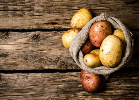pile: Fresh potatoes in an old sack on wooden background