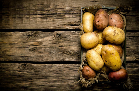 papas: Patatas en una vieja caja de madera sobre una mesa Foto de archivo