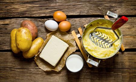 patatas: Ingredientes para el puré de patatas - huevos, leche, mantequilla y patatas en el fondo de madera. Vista superior