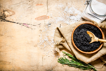 Black caviar in a cup with salt and rosemary On a wooden table.