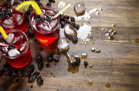 blackberry fruit: Making a cocktail of berries, ice and lemon on wooden background.