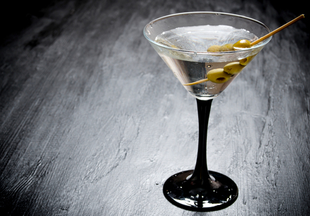 sweet vermouth: Martini with olives on a black table. Stock Photo