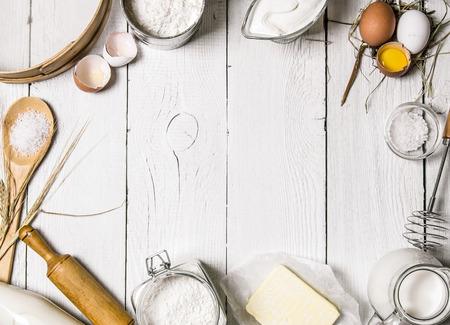 Zutaten für den Teig - Milch, Eier, Mehl, saure Sahne, Butter, Salz und verschiedene Werkzeuge auf einem weißen hölzernen Hintergrund. Standard-Bild - 50024827