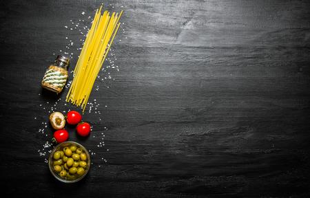 gli spaghetti secchi con olive, pomodori e sale su uno sfondo di legno nero.