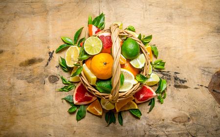 fruits in a basket: The concept of citrus. Basket of citrus fruits - grapefruit, orange, tangerine, lemon, lime On a wooden table. Top view Stock Photo