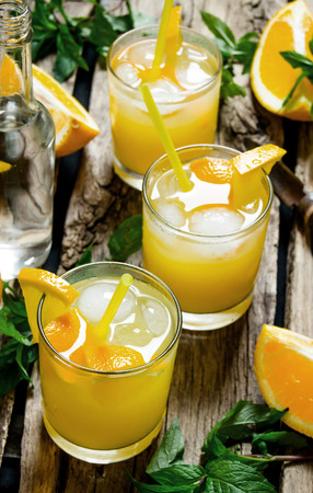 alcohol screwdriver: Fresh orange cocktail. Three cocktails from fresh oranges with ice and mint leaves on wooden background