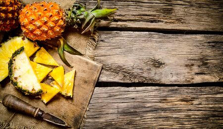 Sliced fresh pineapple with a knife on a chopping Board. On wooden background. Reklamní fotografie
