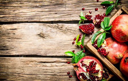 Fresh pomegranates in an old box with leaves. On wooden background.