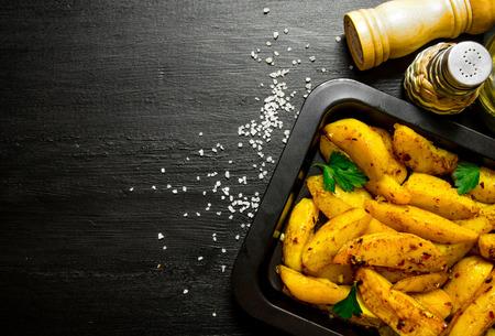 검은 나무 테이블에 향신료와 소금 구운 감자. 스톡 콘텐츠