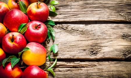 Fresh red apples with green leaves on wooden table