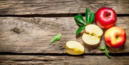 manzana roja: Manzanas rojas frescas con hojas verdes sobre la mesa de madera