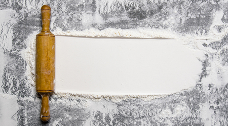 The rolling pin with flour on a stone background. 版權商用圖片
