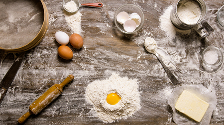 wooden surface: Flour with egg and other ingredients On a wooden table.