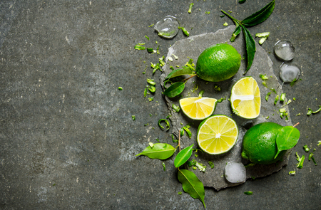ice cube: Slices of lime with ice and leaves on a stone stand On the stone table. Stock Photo