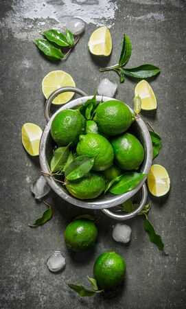 lime: Fresh limes in a saucepan with slices and leaves around. On the stone table. Top view Stock Photo