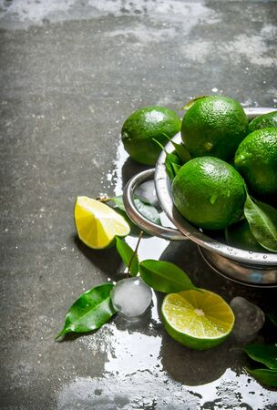 pan tropical: Fresh limes in a saucepan with slices and leaves around. On the stone table.