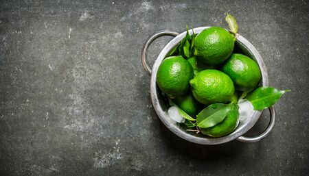 lime fruit: Fresh limes in a saucepan with the leaves On the stone table.