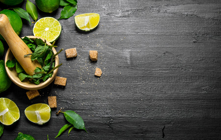 sour grass: The mortar with mint, sugar, lime slices and leaves On a black wooden background.