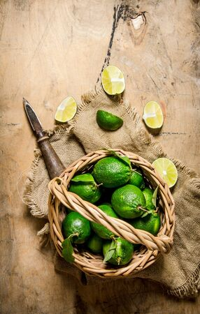 wooden basket: Fresh limes in the old basket on the fabric. On a wooden table. Top view