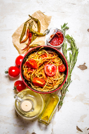 tomato paste: Spaghetti with tomato paste, hot Chili peppers and olive oil. On rustic background. Top view Stock Photo