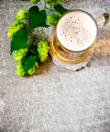 tankard: Glass of beer and green hops. On the stone surface.