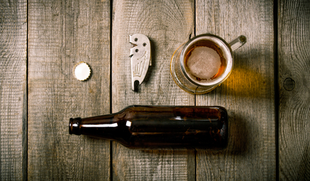 botellas de cerveza: Beer set: bottle, glass of beer, a bottle opener, cork on wooden background.