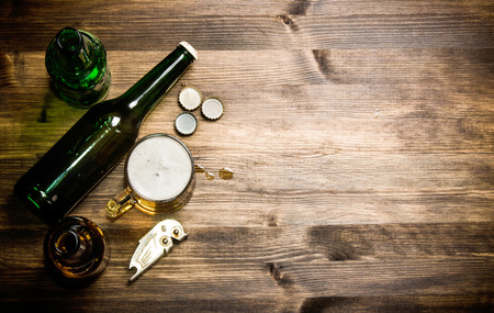 bottle cap opener: Beer style - bottle, beer in the glass and covers on wooden table.