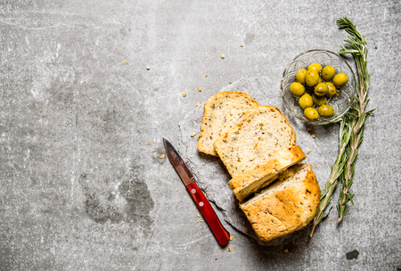 on stones: Bread with olives and rosemary on a stone pedestal. On the stone table.