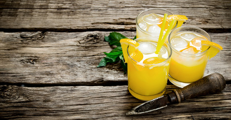 alcohol screwdriver: cocktail of fresh oranges with ice and straw on wooden background