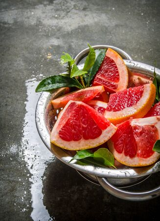 pan tropical: The cut grapefruit with leaves in a saucepan. On the stone table.