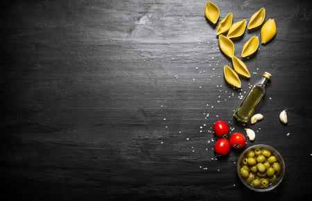Droge deegwaren met olijfolie en tomaten. Op een zwarte houten achtergrond.