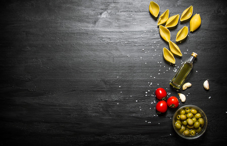 black board: Dry pasta with olive oil and tomatoes. On a black wooden background.