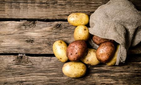 木製の背景に古い袋に新鮮なジャガイモ。