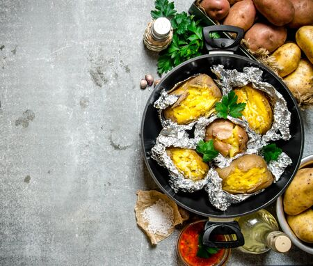 dinner jacket: The concept of baked potato in foil on an old rustic table