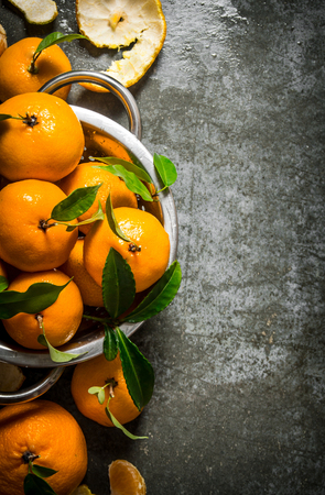 Fragrant fresh tangerines in a saucepan with the leaves On a stone background. Top view