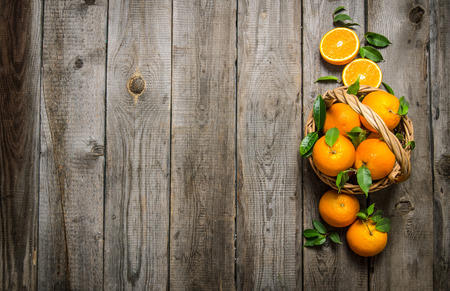 Fresh oranges in the basket with leaves. On a wooden table. Free space for text . Top view Reklamní fotografie