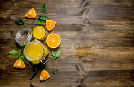 Freshly squeezed orange juice in a jar with bits of around. On a wooden table. Free space for text . Top view